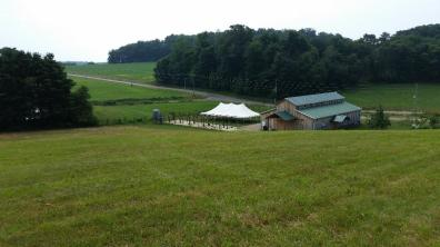Looking down onto a the barn and a tent at a wedding at White Pine grove.