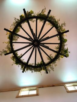 Handmade by owner David Laub, this Rustic Wrought Iron chandelier is decorated with greens for summer.